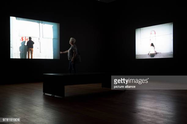 A woman watching videos at the exhibition 'Covered in Time and History The Films of Ana Mendieta' at Martin Gropius Bau Photo Lisa Ducret/dpa
