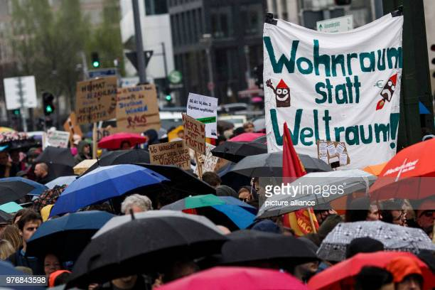 April 2018, Germany, Berlin: Portestors demonstrate against housing shortage and rent increases and carry a sign reading 'Wohnraum statt Weltraum! ....