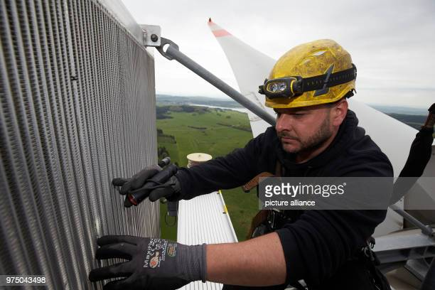 Controller Christoph Lober checking the cooler on the roof of a wind turbine The machines rotor blades and the supporting structure are being...
