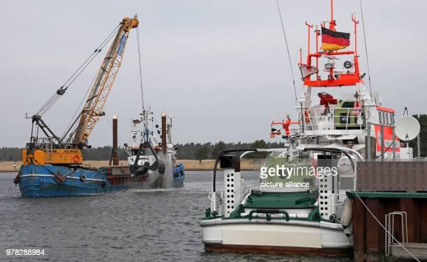A working vessel discharging the dredged up sand next to the rescue cruiser in the Darsser Ort emergency port in the core area of the Western...