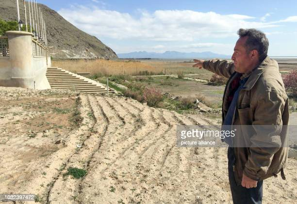 An Iranian man stands at the entrance of the closed beach hotel Fanus It shows where the waves of Lake Urmia came to until a few years ago With the...