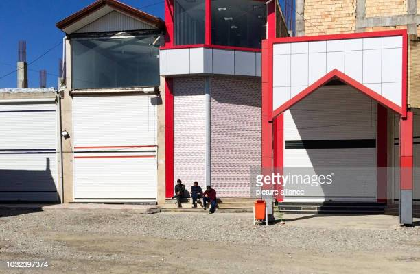 Three Iranian workers are sitting in front of closed shops in the Sero border market near the IranianTurkish border in northwest Tira With the...