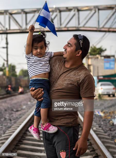 A man carries a child on his arm who is holding the national flag of El Salvador in her hand as the wait for further transportation through Mexico...