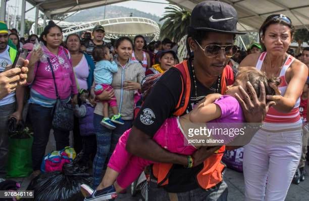 A young man carries a child in his arms on their way with other Central American migrants through Mexico Numerous migrants from Honduras Guatemala...
