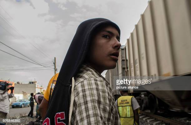 A young man stands in front of a train as he waits for further transportation through Mexico Every year numerous migrants from Honduras Guatemala and...