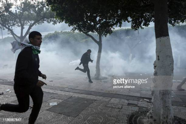 Algerian protesters run for cover from tear gas fired by security forces during an antigovernment demonstration Thousands of Algerians defied police...