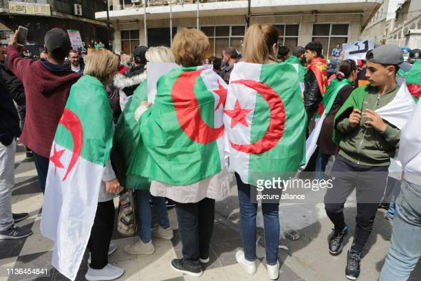 Algerian women wear the Algerian flag as they take part in protest against the newly appointed interim president Abdelkader Bensalah Photo Farouk...