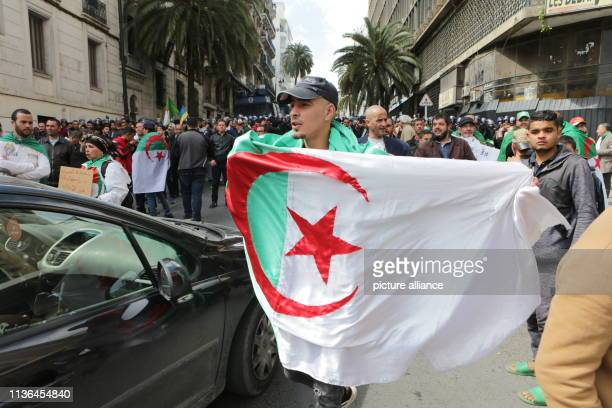 An Algerian man holds the Algerian flag as he takes part in protest against the newly appointed interim president Abdelkader Bensalah Photo Farouk...