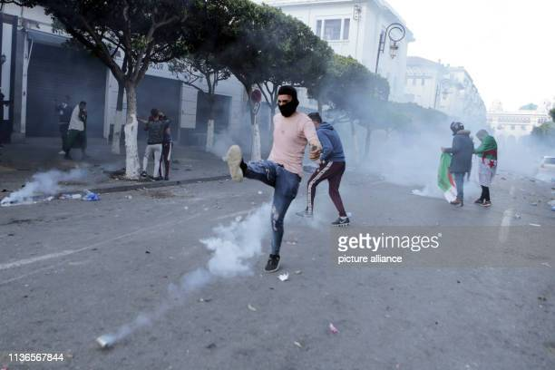 An Algerian protester kicks back a tear gas canister fired by Algerian security forces during clashes that followed an antigovernment demonstration...