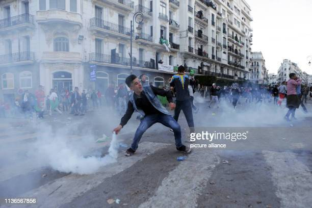 April 2019, Algeria, Algiers: An Algerian protester throws back a tear gas canister fired by Algerian security forces during clashes that followed an...
