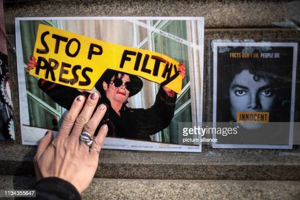 A fan grasps by hand on a picture of Michael Jackson with the inscription Stop Filthy Press placed at the monument to Jackson in front of the...