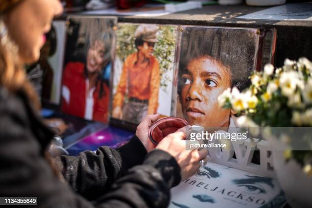 A fan lights a candle at the monument to Michael Jackson in front of the Bavarian Court Photo Sina Schuldt/dpa
