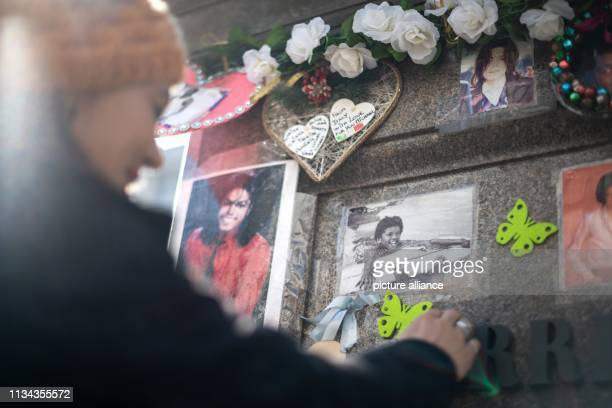 A fan shows children photos of Michael Jackson at the monument for Jackson in front of the Bavarian Court Photo Sina Schuldt/dpa