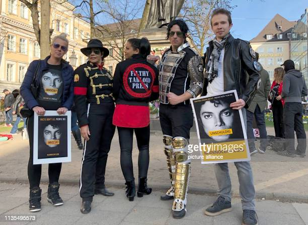 Fans of the King of Pop Michael Jackson and fans with posters with the inscription Innocent stand in front of the monument to OrlandodiLasso a...