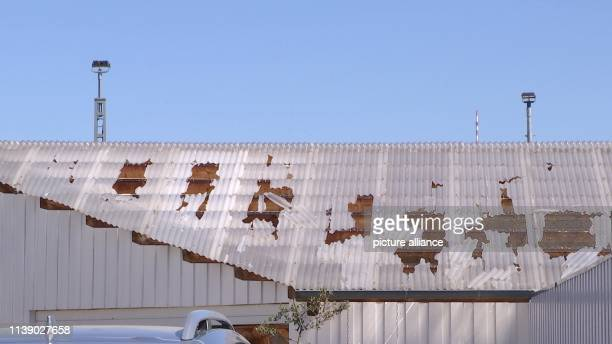Damage can be seen on a roof after an aircraft bomb has been detonated The bombing of the aircraft damaged some of the surrounding buildings on...