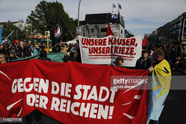 """April 2019, Berlin: Participants of a demonstration walk with banners with the inscription """"Gegen die reiche Stadt"""" and """"Unsere Häuser unsere Kieze""""..."""