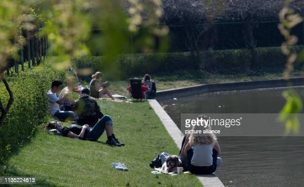 People enjoy the warming sunrays at the edge of the Engelbecken in Kreuzberg Photo Paul Zinken/dpa