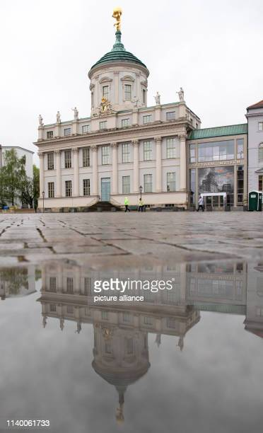 The Old Town Hall on the Old Market Square is reflected in a puddle in rainy weather Photo Ralf Hirschberger/dpa