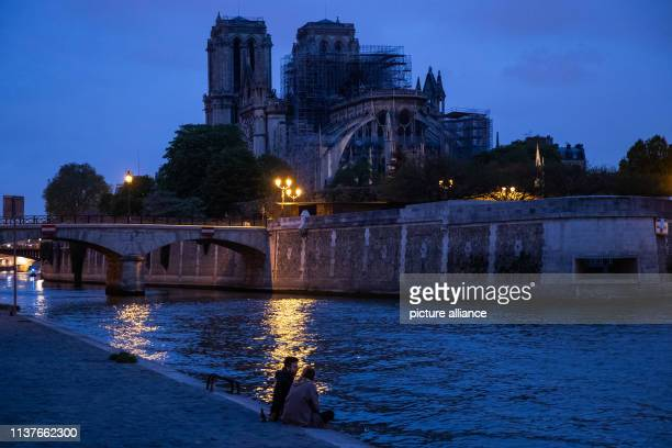 A man and a woman sit on the Seine at blue hour In the background the Paris cathedral NotreDame shines weakly A fire broke out in the worldfamous...