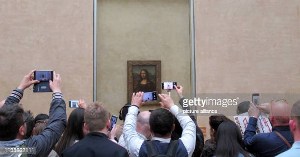 "April 2019, France , Paris: Visitors stand with their mobile phones and smartphones in front of Leonardo da Vinci's ""Mona Lisa"" in the Louvre. Day..."