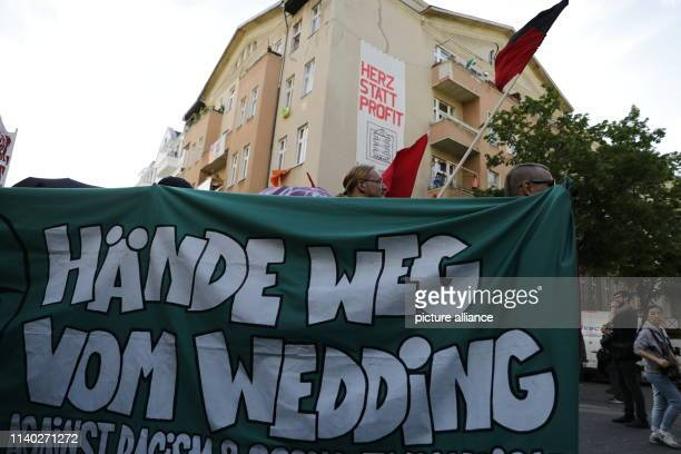 """April 2019, Germany , Berlin: Participants of a demonstration walk through the Wedding district with a banner saying """"Hands off Wedding"""". The..."""