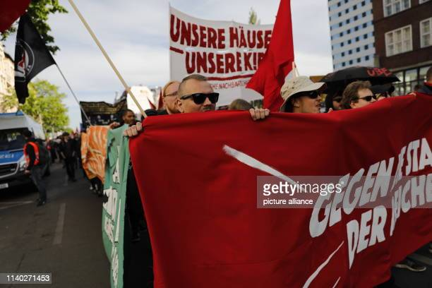 """April 2019, Germany , Berlin: Participants of a demonstration walk with banners with the inscription """"Gegen die Stadt der Reichen"""" and """"Unsere Häuser..."""