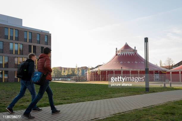08 April 2019 Lower Saxony Braunschweig Two students approach a circus tent standing on an open space next to buildings of the Technical University...
