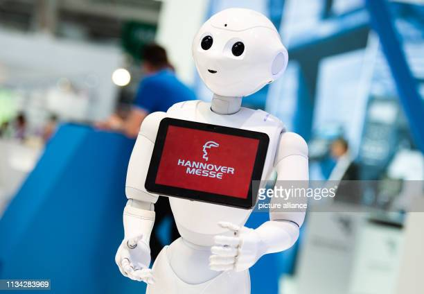 The robot Pepper of the manufacturer SoftBank Robotics stands at the Hanover Fair at the booth of Konica Minolta and shows the logo of the fair Photo...