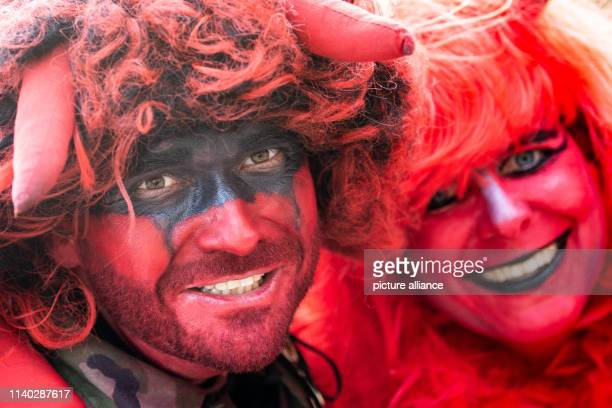 30 April 2019 Lower Saxony St Andreasberg Participants of the Walpurgis celebration dressed as two devils pose in the spa park Walpurgis is...