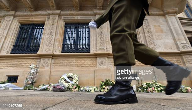 April 2019, Luxembourg, Luxemburg: A guard walks past laid flowers and wreaths in front of the Grand Ducal Palace in Luxembourg. The body of the...