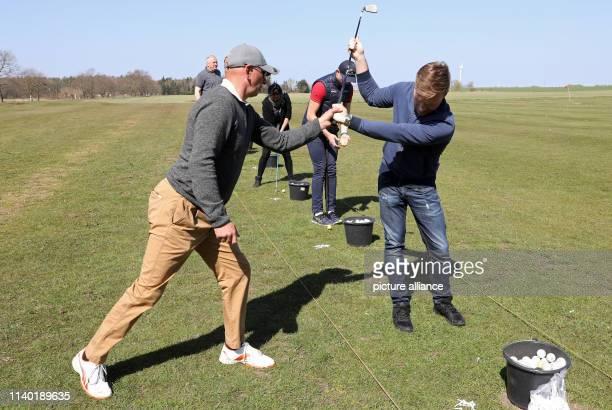19 April 2019 MecklenburgWestern Pomerania RibnitzDamgarten Golf instructor Tom Siegfried and Philipp Braun practice the right tee shot at a golf...