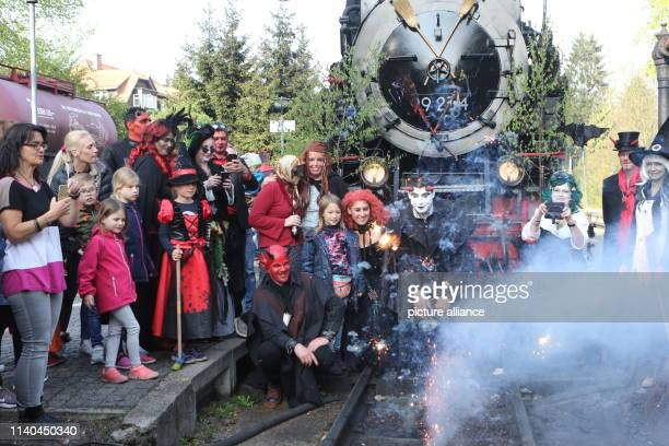 30 April 2019 SaxonyAnhalt DreiAnnenHohne People dressed as witches and devils stand in front of the steam engine of the Walpurgis train at the...