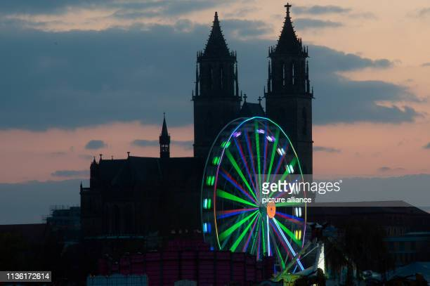 The brightly coloured Ferris wheel of the spring fair turns after sunset in front of the silhouette of the cathedral Photo KlausDietmar...