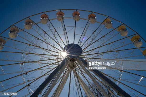 The sun shines through the spokes of the Ferris wheel of the spring fair At the beginning of the week the sun shines from a cloudless sky in the...