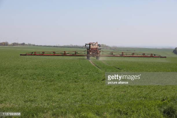 An agricultural machine drives over a field and sprays the crop Photo Bodo Schackow/dpa