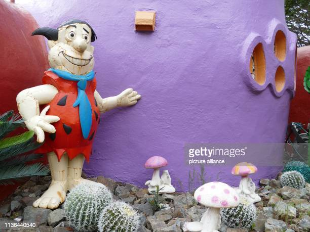 A figure of Fred Feuerstein stands in front of a colourfully painted house in an unusual style in Hillsborough near San Francisco A Californian...