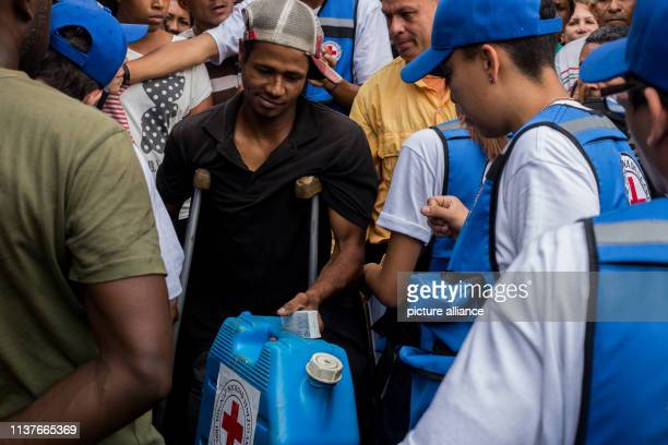 A man with crutches receives water treatment tablets and a canister First relief supplies of the Red Cross have arrived in Venezuela Photo Ruben...