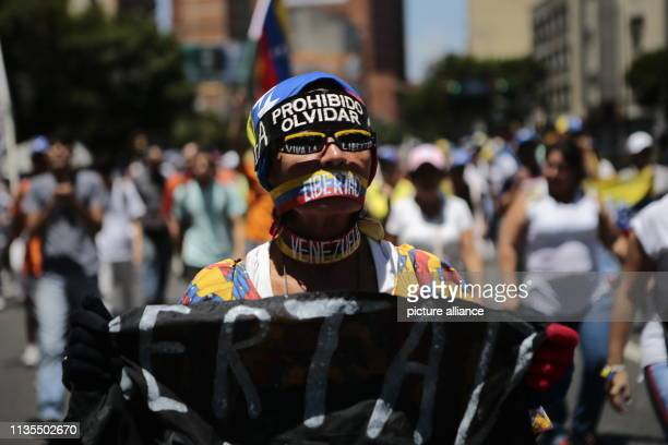 A woman in a cap with the slogan Prohibido Olvidar walks on the street during a protest rally against the Venezuelan government At the rally the...