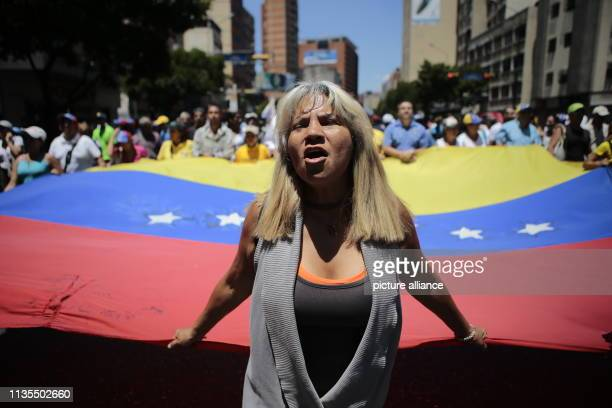 A woman walks in front of the country's flag during a protest rally against the Venezuelan Government At the rally the selfproclaimed interim...