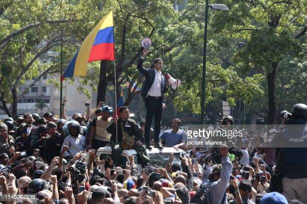 Juan Guaido selfproclaimed interim president of Venezuela stands with two megaphones in his hands surrounded by soldiers and civilians at Plaza...