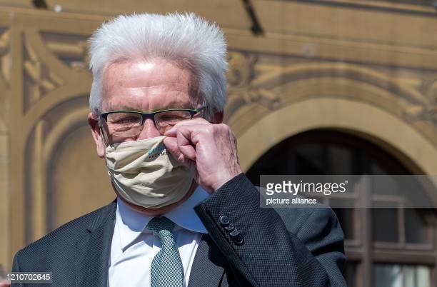 Winfried Kretschmann Minister President of BadenWürttemberg puts on a breathing mask with the inscription Wir halten zusammen Auch mit Abstand over...