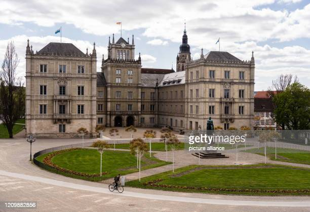 April 2020, Bavaria, Coburg: A cyclist rides past Ehrenburg Castle on the empty Schlossplatz. Photo: Nicolas Armer/dpa