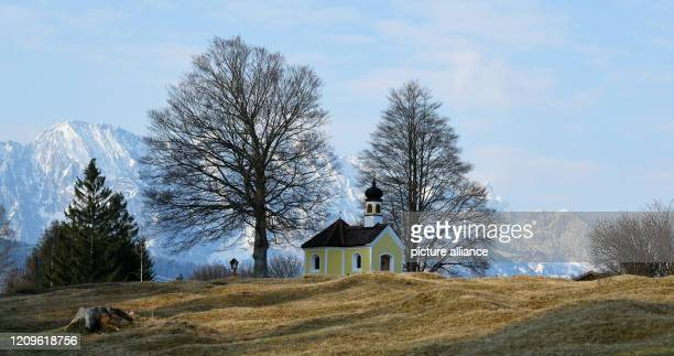 April 2020, Bavaria, Krün: The sun rises at the chapel Maria Rast in the humpback meadows, with the peaks of the Wettersteingebirge in the...