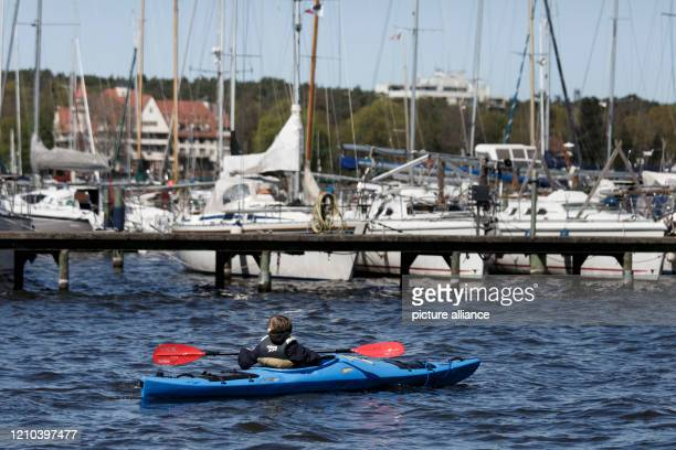 April 2020, Berlin: A man in a paddleboat passes a sailboat harbour on the Wannsee. During the curfew in the Corona crisis many people take advantage...