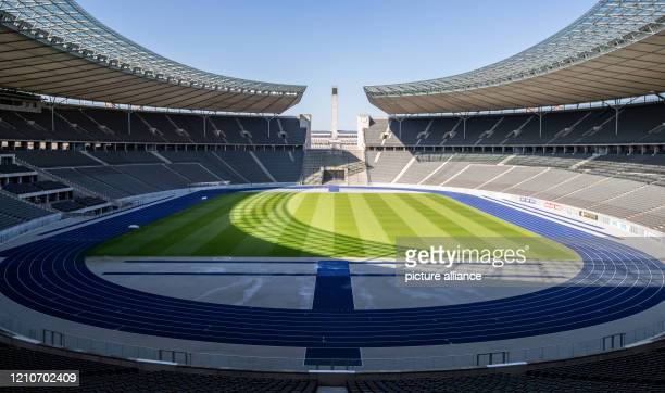 April 2020, Berlin: A view over the Olympiastadion Berlin shows empty tiers and deserted lawns in bright sunshine. Due to measures to contain the...