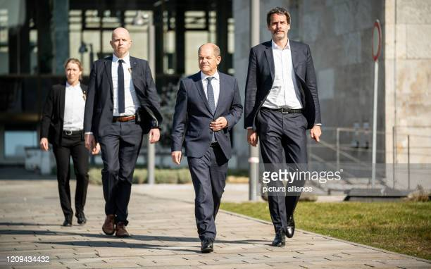 Olaf Scholz Federal Minister of Finance joins Steffen Hebestreit press spokesman of the ministry and bodyguards for a press conference after the...