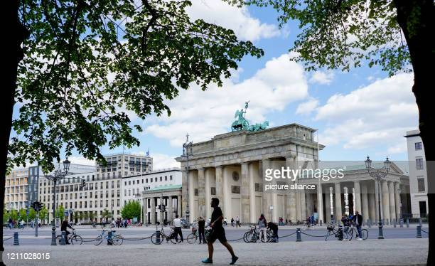 April 2020, Berlin: Only a few people can be seen on Sunday on the west side of the Brandenburg Gate. Photo: Jörg Carstensen/dpa