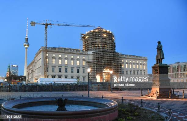 April 2020, Berlin: The facade of the Berlin Palace at dusk in the evening. On the left the Marienkirche, the Park Inn Hotel, the television tower...