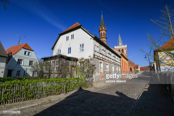 April 2020, Brandenburg, Lieberose: View of the Kantorschulhaus built around 1800, behind it the protestant country church Lieberose and behind it...