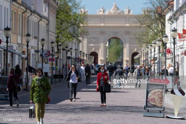 April 2020, Brandenburg, Potsdam: A woman with a face mask and shopping bag is walking on the shopping mile Brandenburger Straße coming from the...
